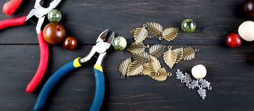 Tools for handmade jewelry. Beads, plier and wire. Tools for handmade jewelry. wooden Beads, plier and accessories to create hand made fashion jewelry on dark stock photos