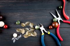 Tools for handmade jewelry. Beads, plier and wire. Tools for handmade jewelry. wooden Beads, plier and accessories to create hand made fashion jewelry on dark stock image