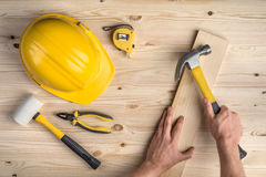 Tools and hands working with hammer on wooden background Royalty Free Stock Photo