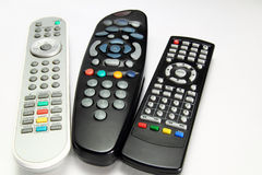 Tools for human happyness. Three remote controls for digital player , television and pay television Stock Photography