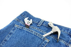 Tools In Jean Pocket. A wrench and a small hammer stick out of the top of a pocket on the back of a pair of denim blue jeans Stock Photos
