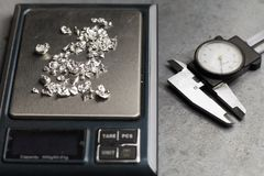 Tools of jewellery. Jewelry workplace on metal background. Weigh-scales with granules of silver.  Royalty Free Stock Photography