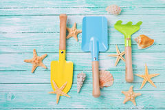 Tools for kids for playing in sand  and sea object on turquoise. Painted wooden planks. Place for text. Vacation background Stock Photo
