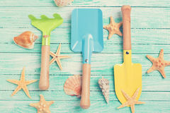 Tools for kids for playing in sand  and sea object on turquoise. Painted wooden planks. Place for text. Vacation background. Toned image Royalty Free Stock Photography