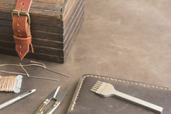 Tools for leather and chest stands on a piece of leather Royalty Free Stock Photo