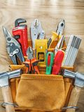 Tools in leather toolbelt on wooden board top view.  Stock Photo