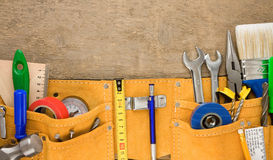 Tools in leathern belt on wood Royalty Free Stock Photography