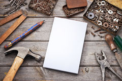 Tools List Note Background. A tool workbench with notepad, pencil, hammer, nails and screws in old tin boxes Stock Images
