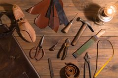 Tools for making shoes lie on a wooden table. Set of items symbolizing manual labor, small business stock image