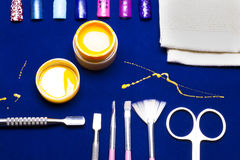Tools for manicure, gel nail color yellow, messy shed foreman at the blue table. Resistant. Manicure royalty free stock photography
