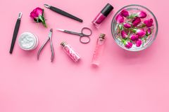 Tools for manicure with spa salt and rose on pink background top view mockup. Tools for manicure with spa salt and rose on pink desk background top view mockup stock photo