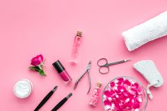 Tools for manicure with spa salt and rose on pink background top view mockup. Tools for manicure with spa salt and rose on pink desk background top view mockup stock image