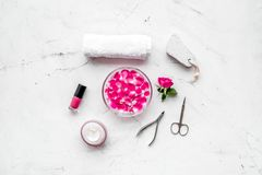 Tools for manicure with spa salt and rose on white stone background top view space for text. Tools for manicure with spa salt and rose on white stone desk royalty free stock photos