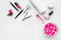 Tools for manicure with spa salt and rose on white stone background top view space for text. Tools for manicure with spa salt and rose on white stone desk stock photography