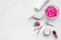 Tools for manicure with spa salt and rose on white stone background top view space for text. Tools for manicure with spa salt and rose on white stone desk royalty free stock photo