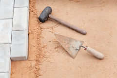 Tools of the mason on a sand - trowel and hammer Royalty Free Stock Photos