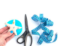 Tools and materials for creativity and Hobbies. The scissors in the girls hand. White background. Tape, tapes, star, and fish tissue Royalty Free Stock Photography