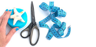 Tools and materials for creativity and Hobbies. The scissors in the girls hand. White background. Tape, tapes, star, and fish tissue Royalty Free Stock Images