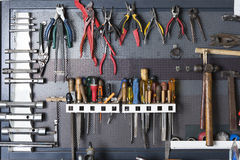 Tools on a metal board. Mechanic tools hanging on a organized metal board at a vehicle reparation workshop Royalty Free Stock Photography