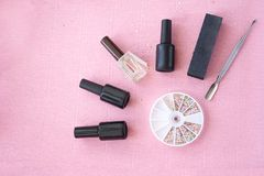 Tools for nail design top view: bottles of gel polish and foils on pink background. Tools for nail design top view: bottles of gel polish and foils on pink Royalty Free Stock Image