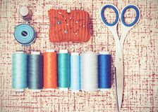 Tools for needlework, red knitted needle pad for sewing, scissors and colored thread coils on brown background with copy space for stock photos