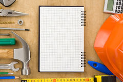 Tools and notebook on wood Royalty Free Stock Photos
