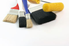 Tools for painting. Detail from four paint brushes and paint roll on white background hardware tools with copy space stock images