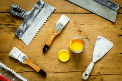 Tools for painting on a wooden table with yellow paint Stock Photos