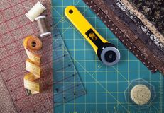 Tools for the patchwork on the mat for patchwork. On the mat for patchwork sewing there are scissors, a knife for patchwork, a ruler, a patchwork napkin and royalty free stock photos