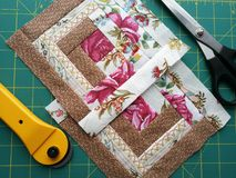 Tools for patchwork on the mat for patchwork. On the mat for patchwork sewing there are scissors, a knife for patchwork,  a patchwork napkins Royalty Free Stock Photos