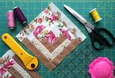 Tools for patchwork on the mat for patchwork. On the mat for patchwork sewing there are scissors, a knife for patchwork, a ruler, a patchwork napkin and threads Royalty Free Stock Photo