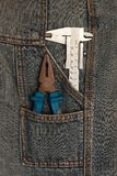 Tools pliers and micrometer in jeans pocket Royalty Free Stock Photos