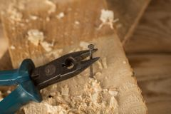 Tools. pliers pull the nail out of the wooden board stock photography
