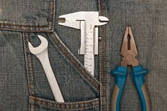 Tools pliers, spanner and micrometer in jeans pocket Stock Photo