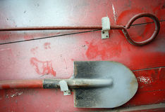 Tools for precaution. Shovel and breakage on a dusty red board Royalty Free Stock Photo