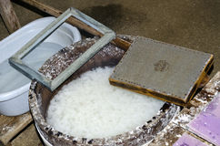 Tools for producing handmade paper. Tub with pulp, wire mesh and frame to produce handmade paper stock image
