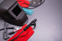 Tools and protective welding clothing. Welding equipment, welding mask, protective leather gloves, welding electrodes, high-voltage wires with clamps, cutting Stock Image