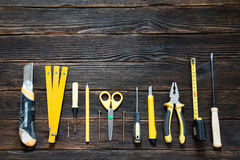 Tools for repair and construction in yellow. View from above: tape measure, pencil, screws, scissors, screwdriver, knife for paper and plastic pliers. On a Royalty Free Stock Photography