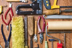 Tools for repair: roller, chisel, pliers, glass cutter, hammer on a wooden background.  stock photo