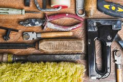 Tools for repair: roller, chisel, pliers, glass cutter on a wooden background.  royalty free stock photo