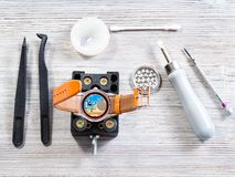 Tools for replacing battery in quartz wristwatch. Watch repairer workshop - set of tools for replacing battery in quartz wristwatch on wooden table royalty free stock images