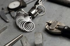 Tools set of jewellery. Jewelry workplace on metal background. Finger sizing for rings, beam compass, pincer, nippers Stock Photography