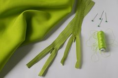 ..tools for sewing and needlework. green threads and green fabric stock photo