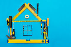 Tools in the shape of house over blue background. Stock Photo