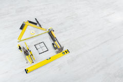 Tools in the shape of house over wooden floor Stock Photos