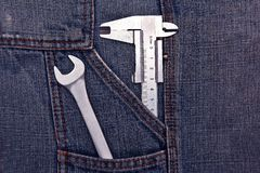 Tools spanner and micrometer in jeans pocket Stock Image