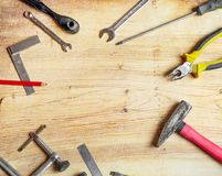 Tools spread out on the board, screwdrivers, pliers, wrenches, squares. Flat lei composition, frame Stock Images