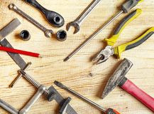 Tools spread out on the board, screwdrivers, pliers, wrenches, squares. Flat lei composition, frame Royalty Free Stock Photo