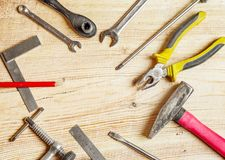 Tools spread out on the board, screwdrivers, pliers, wrenches, squares. Flat lei composition, frame Stock Photography