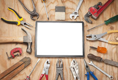 Tools Computer Tablet Background. A computer tablet surrounded by hand tools on a wood background Stock Images